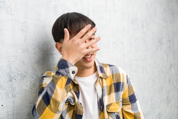 恥ずかしいと同時に笑っている若い中国人男性の顔のクローズアップ