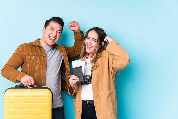 若いカップルは旅行の準備ができて、勝利、勝者の概念の後拳を上げます。