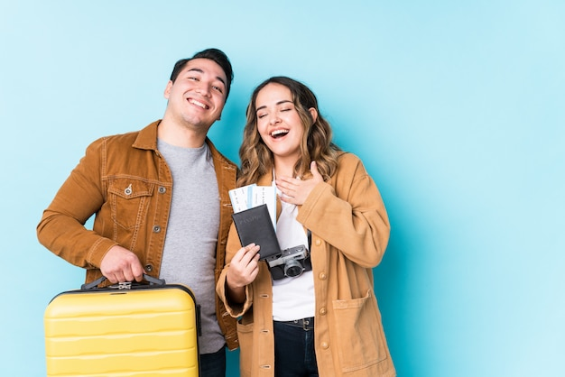 孤立した旅行の準備ができている若いカップルは、胸に手をつないで大声で笑います。