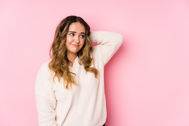 ピンクの壁でポーズをとって若い曲線の女性は、頭の後ろに触れる、考えて、選択を分離しました。