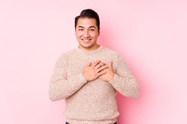 ピンクの壁でポーズをとって若い曲線の男は、心、幸福の概念に手をつないで笑って分離しました。