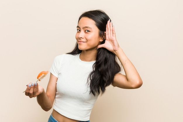ゴシップを聴こうとして寿司を保持している若いアジア女性。
