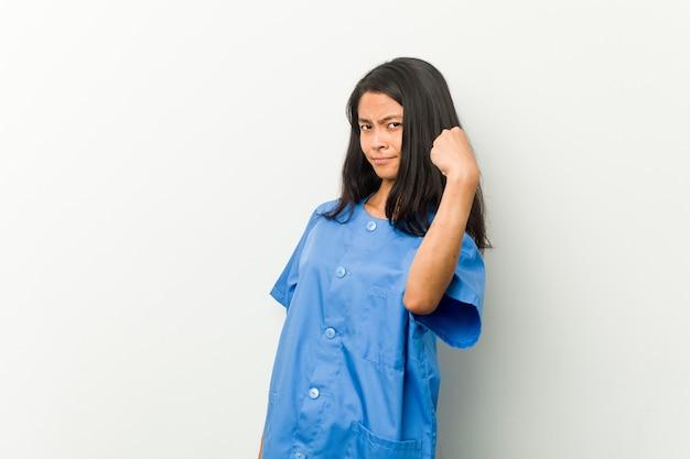 Молодая азиатская женщина медсестры показывая кулак к камере, агрессивное выражение лица.