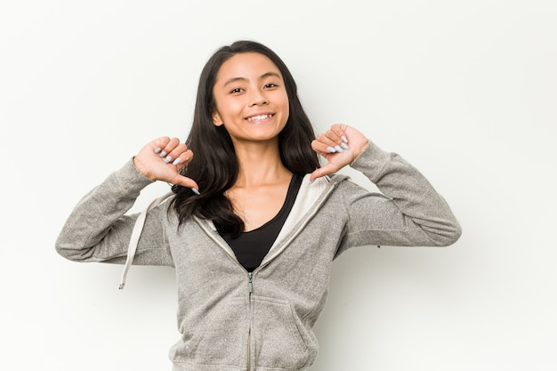 若いフィットネス中国人女性は誇りと自信を持っていると感じています。