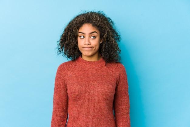 混乱している若いアフリカ系アメリカ人の巻き毛の女性は、疑いと不安を感じています。