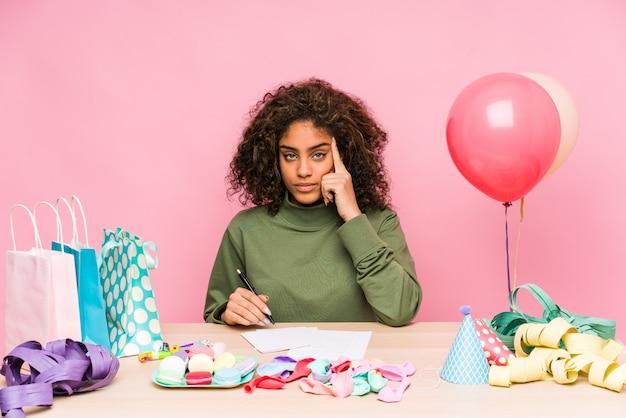 Молодая афро-американская женщина планируя день рождения указывая висок с пальцем, думая, сфокусировала на задаче.