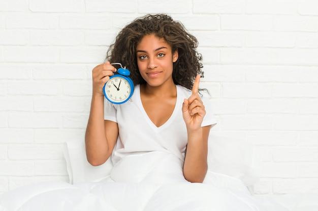 指でナンバーワンを示す目覚まし時計を保持しているベッドに座っている若いアフリカ系アメリカ人女性。