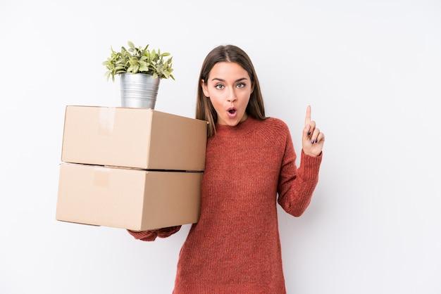 いくつかの素晴らしいアイデア、創造性の概念を持つボックスを保持している若いコーカサス地方の女性。