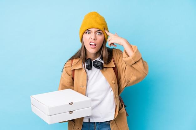 Молодая кавказская женщина держа пиццы изолировала показывать жест разочарования с указательным пальцем.