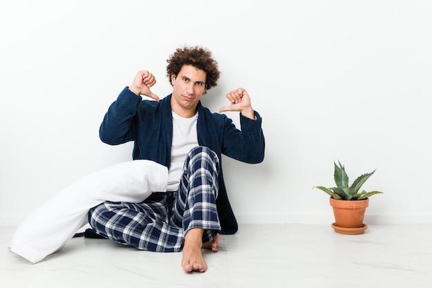 家の床に座っているパジャマを着ている中年の男性は、誇りに思って自信を持っていると感じています。