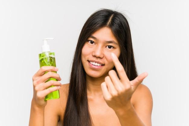 アロエベラと保湿剤を保持している若い中国人女性は、まるで招待が近づくかのように、あなたに指で指します。