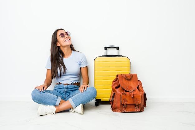 若い混血インドの女性はリラックスして幸せな笑い、首を伸ばして歯を見せて旅行に行く準備ができています。