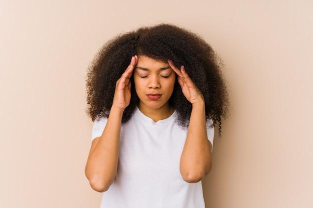 お寺に触れると頭痛を持つ若いアフリカ系アメリカ人女性。