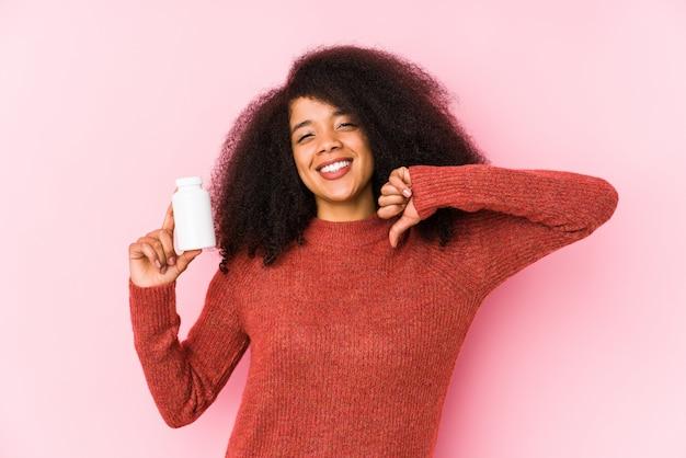 分離されたビタミンを保持している若いアフロ女性ビタミンを保持している若いアフロ女性は、誇りに思って、自信を持って、次の例です。