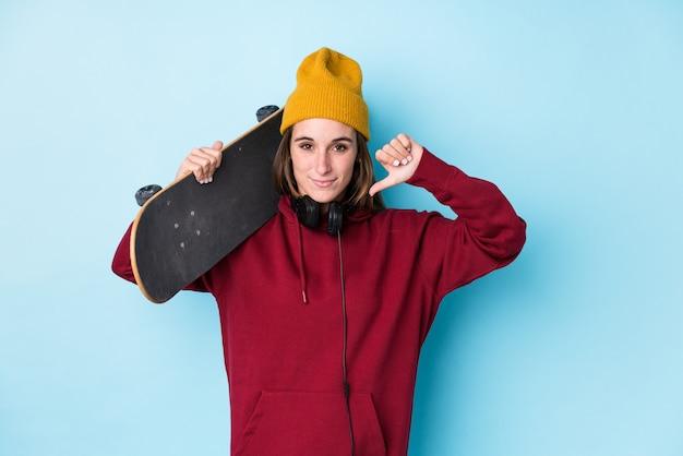 Женщина молодого конькобежца кавказская изолировала показывать жест нелюбов, большие пальцы руки вниз. концепция несогласия.