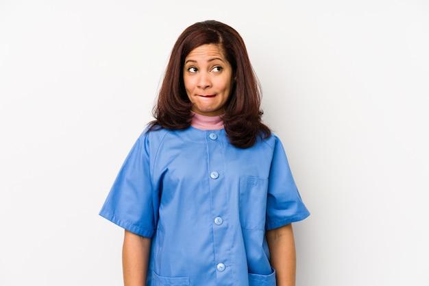 分離された中年のラテン語の看護師の女性は混乱し、疑わしく、自信がありません。