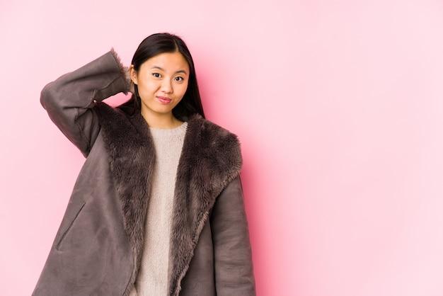 コートを着た若い中国人女性は、頭の後ろに触れて、考えて、選択をしました。