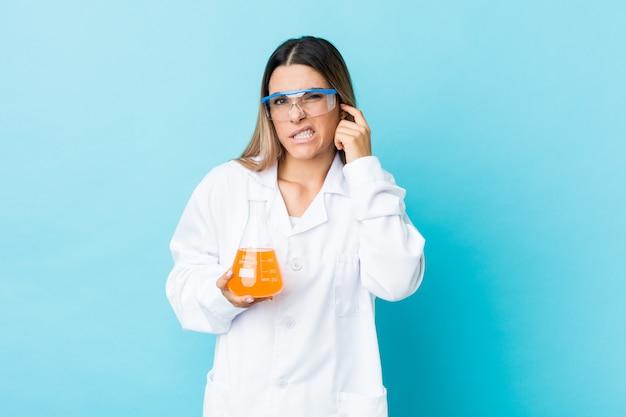 若い科学女性の手で耳を覆っています。