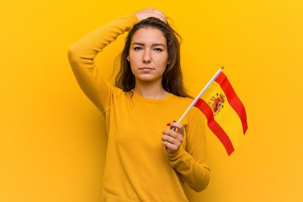 ショックを受けているスペインの旗を保持している若いヨーロッパの女性、彼女は重要な会議を覚えています。