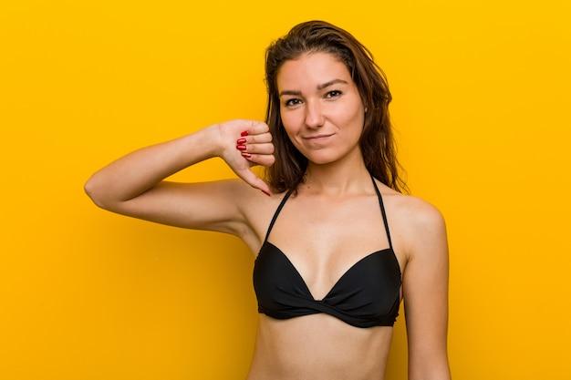 嫌いなジェスチャーを示すビキニを着ている若いヨーロッパの女性は、親指を下げます。不一致の概念。