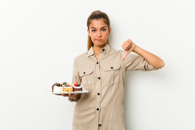 嫌いなジェスチャー、親指ダウンを示す甘いケーキを保持している若い白人女性。不一致の概念。
