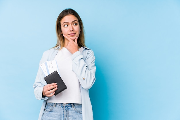 疑わしいと懐疑的な表情で横に見てパスポートを保持している若い白人女性。