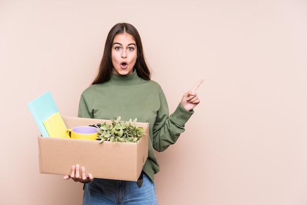 側を指している新しい家に移動する若い白人女性