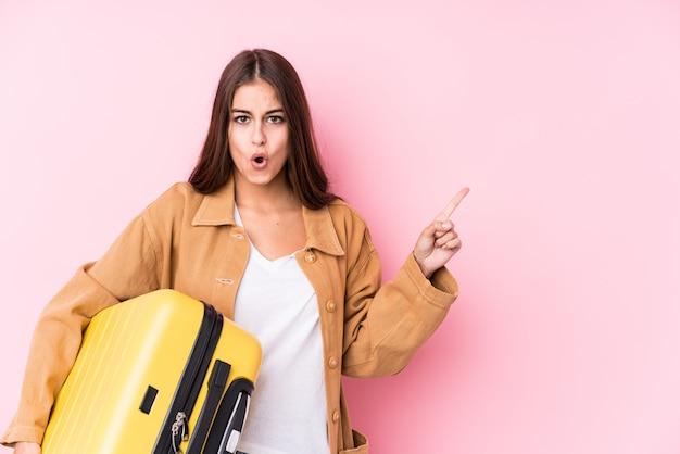 側を指しているスーツケースを保持している若い白人旅行者女性