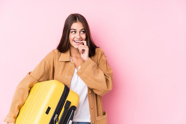スーツケースを保持している若い白人旅行者女性が何かについてリラックスした思考