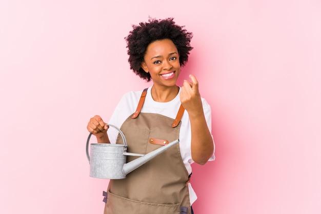 Молодая афро-американская женщина садовника указывая пальцем на вас как будто приглашая приблизиться.