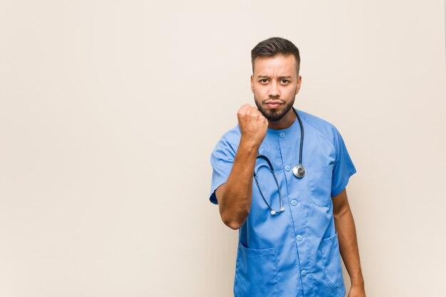 カメラ、積極的な表情に拳を示す若い南アジアの看護師男。