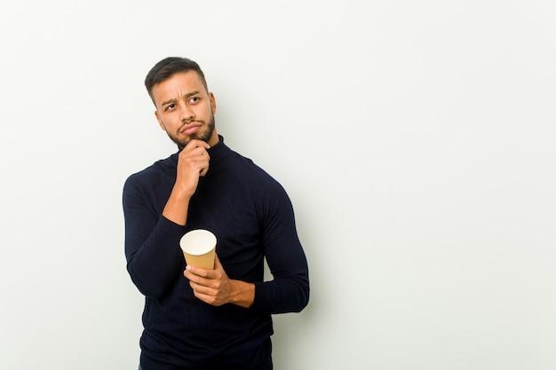 疑わしいと懐疑的な表情で横向きにテイクアウトコーヒーを保持している若い混血アジア人。