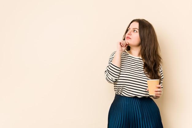 疑わしいと懐疑的な表情で横向きのコーヒーを保持している若い女性。