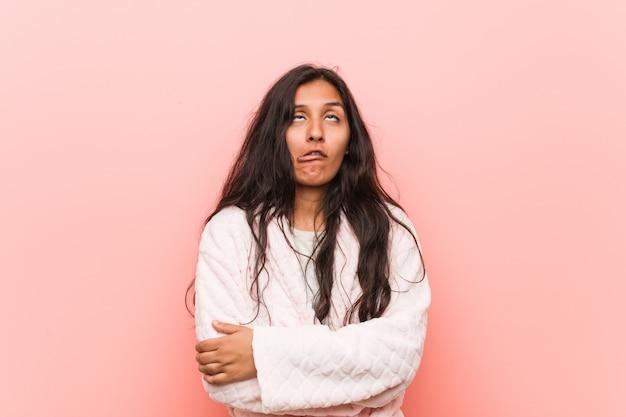 Молодая индийская женщина в пижаме устала от повторяющейся задачи.