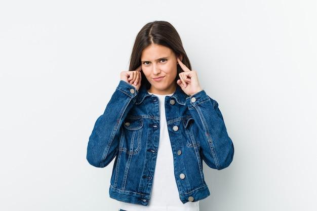 手で耳を覆う若いかわいい女性。
