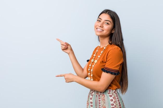 若いアラブ女性は人差し指で離れて指している興奮しています。