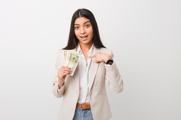 Молодые арабские бизнес женщина, держащая долларов удивлен, указывая на что-то на себя, широко улыбаясь.