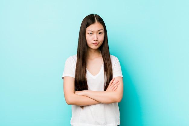 皮肉な表情でカメラで見て不幸な若いかなり中国人女性。