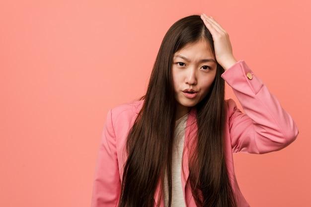 ピンクのスーツを身に着けている若いビジネス中国人女性は疲れて非常に眠い彼の頭に手を保ちます。