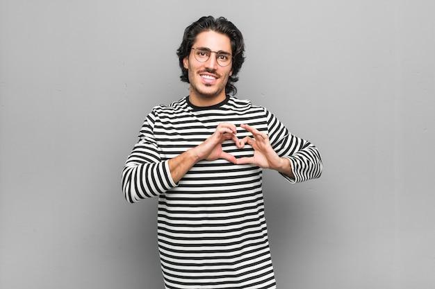 笑みを浮かべて、手でハートの形を示す在庫を保持している若い従業員の男。
