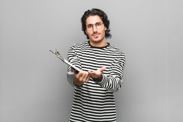 カメラに提供している手のひらで何かを保持している在庫を保持している若い従業員の男。