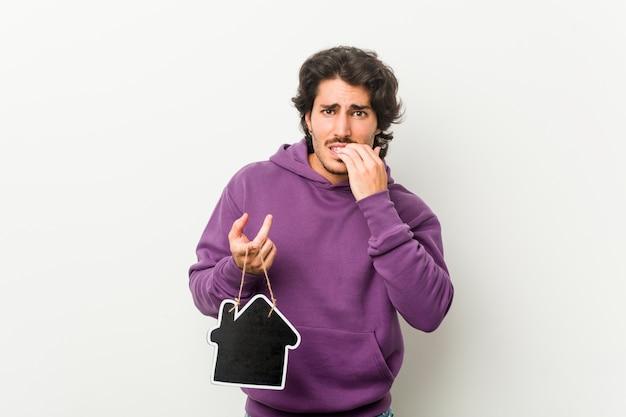 Молодой человек, держащий форму значок дома кусать ногти, нервный и очень тревожно.