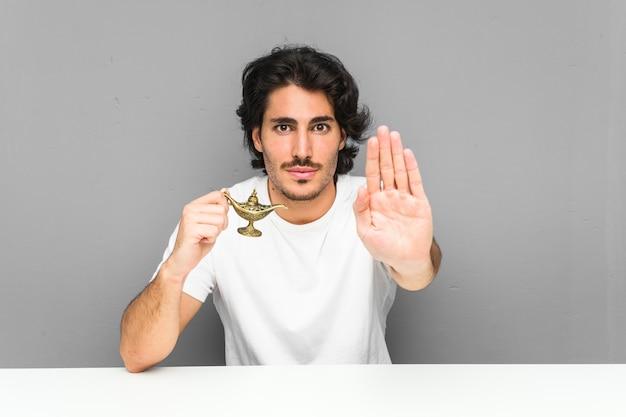 Молодой человек держа волшебную лампу стоя с протягиванной рукой показывая знак стопа, предотвращая вас.