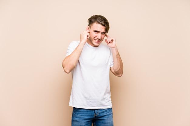Молодой кавказский человек представляя изолированные уши заволакивания руками.