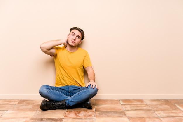 床に座っている若い白人男は、頭の後ろに触れる、考えて、選択を分離しました。