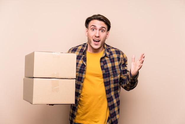 楽しい驚きを受けて、興奮して、手を上げるボックスを保持している若い白人男。