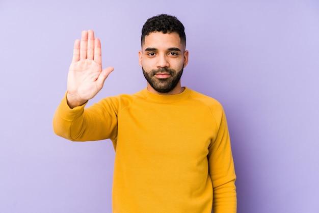 Человек молодой смешанной гонки арабский изолировал положение при протягиванный знак стопа показа руки, предотвращая вас.