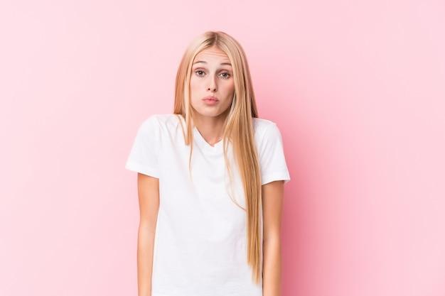 Молодая блондинка на розовом фоне пожимает плечами и смущает открытые глаза.