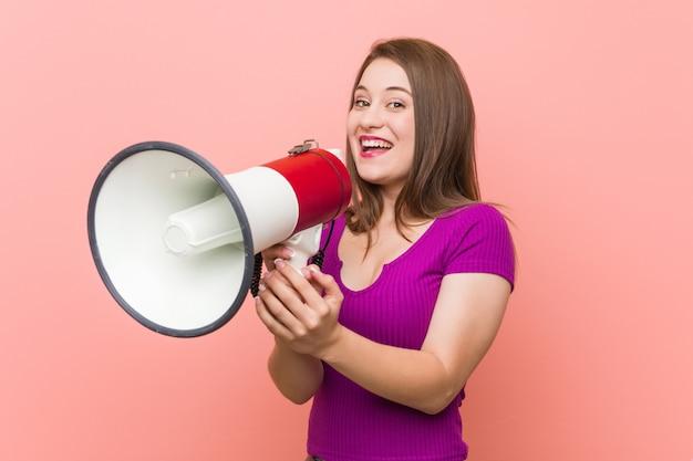 Молодая кавказская женщина говоря через мегафон