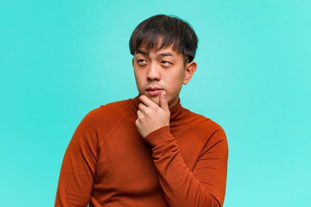 疑って混乱している若い中国人男性